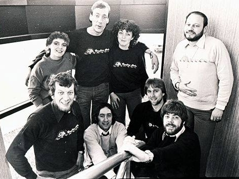 A very early line up from Sunshine Radio: Tony Allan is at the top of the photo with his right arm around  Manon Christie and his left around Siobhán Walls. Peter Madison is standing at the far right.  At the front, from left to right, are Robbie Robinson, Declan Meehan, Timo Jackson and Chris Cary.